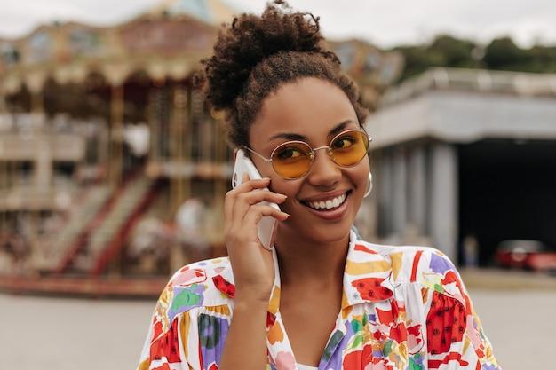 주황색 선글라스를 쓴 꽤 매력적인 젊은 여성이 전화 통화를 합니다.
