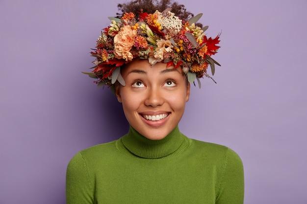 Bella ragazza afro autunnale con espressione felice, guarda sopra la bellissima ghirlanda autunnale realizzata con piante stagionali, indossa dolcevita verde, isolato su sfondo viola.