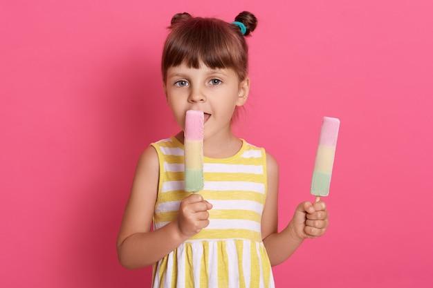 예쁜 아기 여자 아이가 큰 아이스크림을 핥고 다른 하나를 손에 들고, 흰색과 노란색 드레스를 입고, 두 개의 매듭을 가지고.