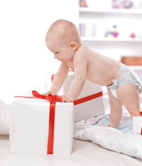 Милый ребенок играет с подарочными коробками. фото с копией пространства