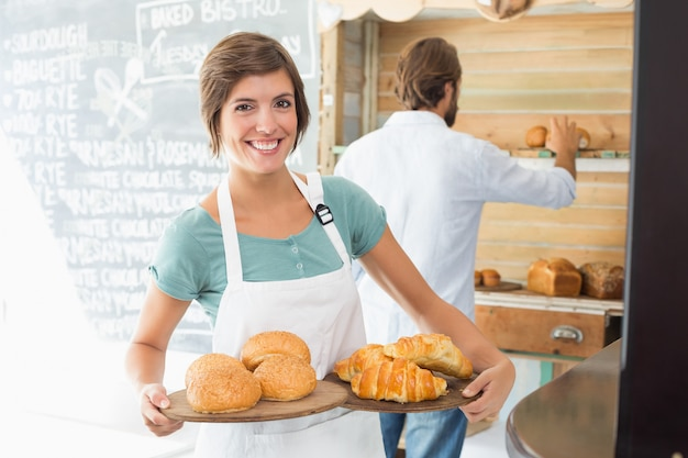 Pretty barista holding trays of baked goods