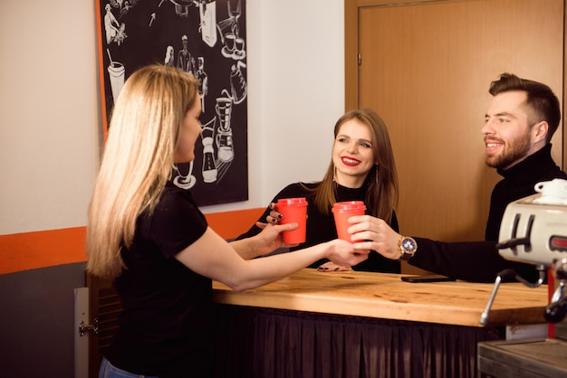 Pretty barista smiling and holding disposable cups at a coffee shop