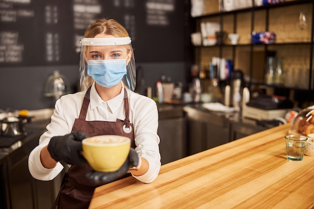Pretty barista with cup of hot cappuccino in hands