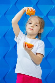흰색 티셔츠를 입은 예쁜 금발 소녀가 파란색 배경에 미소를 짓고 있습니다. 세련된 귀여운 아이가 손에 오렌지 반 개를 들고 있습니다. 감정적 초상화의 개념입니다.