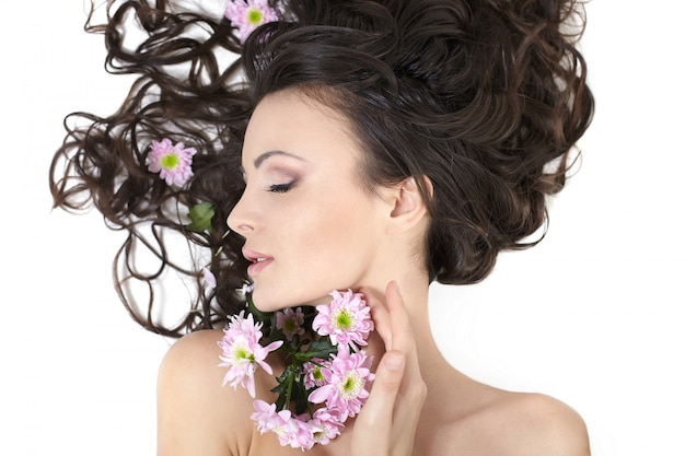 Pretty beautiful girl lying with bright flowers in her hair bright makeup isolated on white