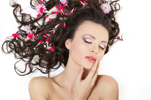 Pretty beautiful girl lying with bright red flowers in her hair bright makeup isolated on white
