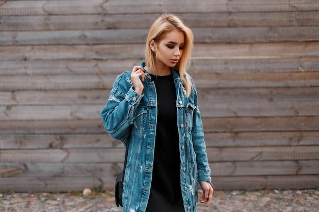 유행 가죽 검은 핸드백과 긴 데님 재킷에 검은 드레스에 꽤 아름 다운 젊은 여자 금발 빈티지 나무 벽 근처에 야외에서 서