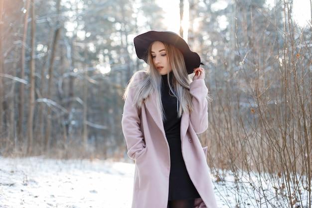 겨울 눈 덮인 공원에서 야외 포즈 세련 된 핑크 코트에 우아한 검은 모자에 검은 니트 드레스에 꽤 아름 다운 젊은 여자. 놀라운 세련된 금발 소녀.