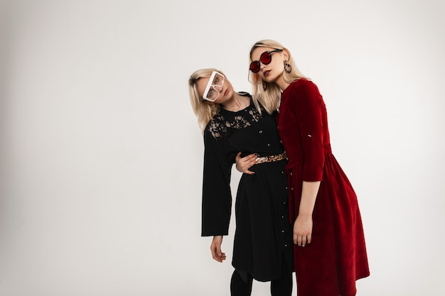 Довольно красивая молодая женщина в модном черном платье в очках обнимает сестру-близнеца в модном красном платье в модных солнцезащитных очках возле старинной стены в помещении