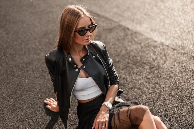 가죽 블랙 재킷에 세련 된 옷에 유행 선글라스에 꽤 아름 다운 젊은 여자는 화창한 여름 날에 포장도에 앉아 쉬고있다. 매력적인 hipster 여자 야외에서 이완.
