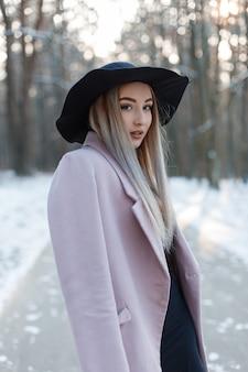 세련 된 겨울 매력적인 옷에 꽤 아름 다운 젊은 여자는 겨울 맑은 날에 눈 덮인 숲에서 세련 된 모자에 간다. 유행 매력적인 세련된 소녀.