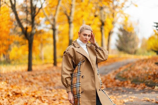 スタイリッシュな髪型のトレンディなベージュのコートでかなり美しい若い女性モデル
