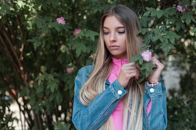 핑크 꽃과 꽃 덤불 근처에 서있는 포즈를 취하는 세련된 데님 재킷에 빈티지 핑크 탑에 자연스러운 메이크업으로 긴 머리를 가진 꽤 아름 다운 젊은 여자. 공원에서 쉬고 귀여운 소녀입니다.