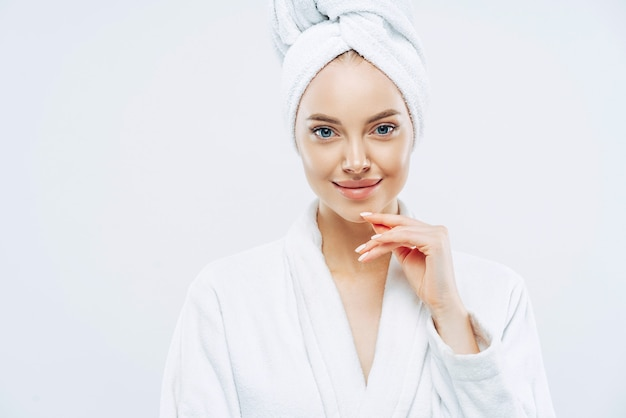 Pretty beauty woman has washed hair, wears wrapped towel on head, has manicure, cute natural face, touches chin gently, looks with tender smile, dressed in bath robe, poses indoor