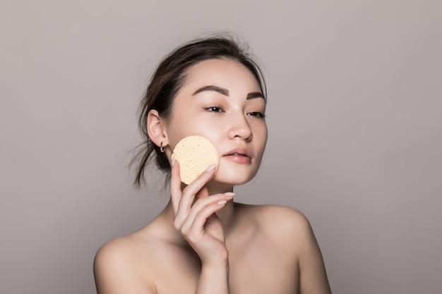 Женщина милой красоты молодая азиатская очищая ее сторону с пусковой площадкой хлопка над белизной изолированной на белой стене. концепция здоровой кожи и косметики.
