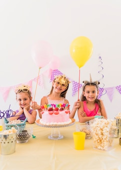 Pretty birthday girl with her friends wearing eye mask standing behind variety of food on table