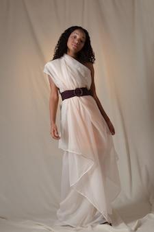 白いドレスを着てフルハイトでポーズをとるかなり黒い女の子。