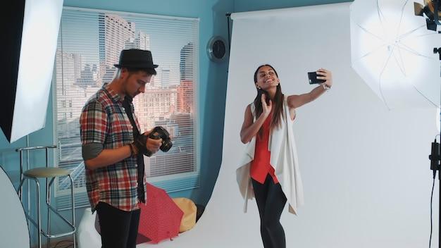 Довольно черная модель делает селфи на смартфоне во время фотосессии в современной студии