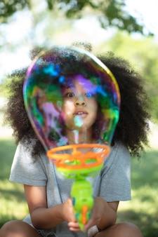 シャボン玉で遊ぶかなり黒い10代の少女