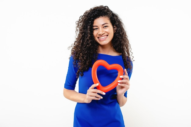 Pretty black woman in blue dress with red heart shape in hands isolated