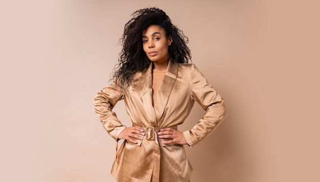Pretty  black woman with beautiful wavy hairs in elegant  golden satin suit posing over beige wall. spring fashion look.