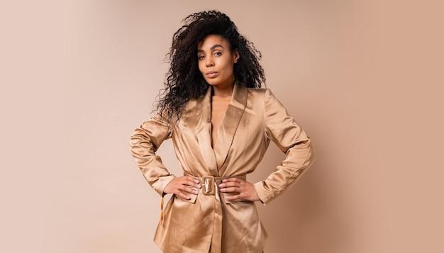 베이지 색 벽 위에 포즈 우아한 황금 새틴 정장에 아름 다운 물결 모양의 머리카락과 함께 예쁜 흑인 여성. 봄 패션 봐.