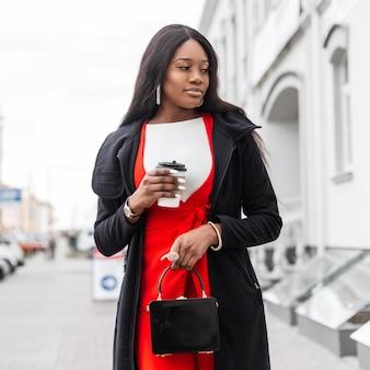 コーヒーとファッションバッグを持つかなり黒人女性が通りを歩きます。スタイリッシュなидфслコートとコーヒーと赤いドレスを着たビジネスアフリカの女の子が街を散歩します