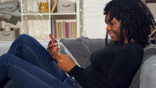 ふわふわの髪を持つかなり黒人女性が本棚のクローズアップでソファーに座っているスマートフォンで銀行カード番号を入力します。