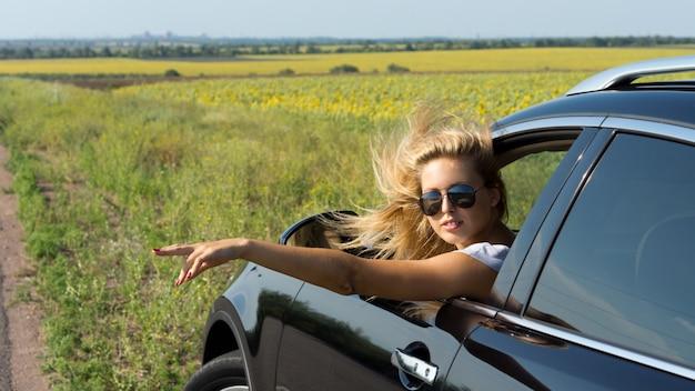 도로로 향하는 손 신호를주는 차창 밖으로 기울고 꽤 단조로운 여성 승객