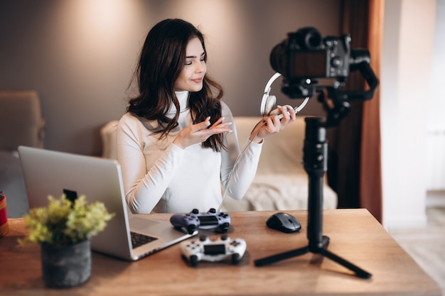 Pretty blogger woman is filming and showing her preference in headphones for video games. influencer young woman live streaming.