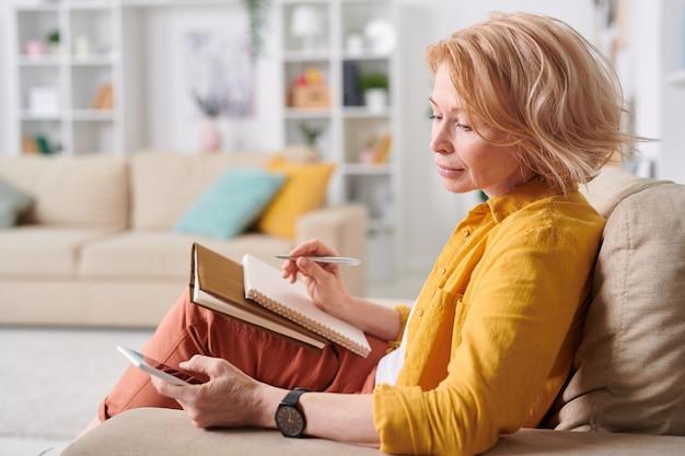 ソファに座って自宅のスマートフォンでスクロールしながら、カジュアルウェアのかなり金髪の女性