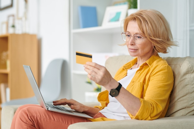 Pretty blond female looking at credit card while scrolling through food products in online supermarket and going to buy some of them