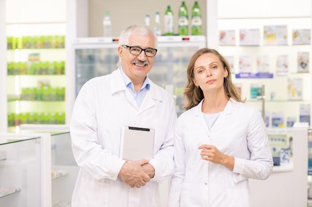 Довольно белокурая женщина-фармацевт и ее старший коллега в белых халатах стоят перед камерой на фоне больших дисплеев с лекарствами