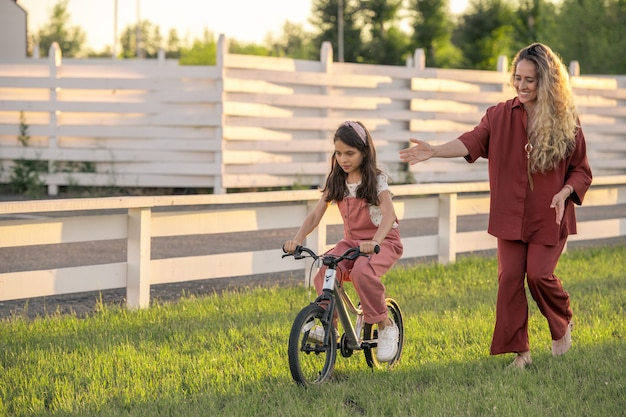 Pretty blond female walking by her little daughter riding bicycle
