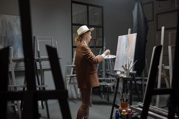 Довольно белокурая женщина с цветовой палитрой стоит перед мольбертом с бумагой во время рисования в классе школы современных искусств