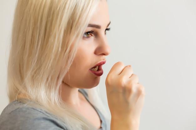 Довольно белокурая девушка кашляет, больна