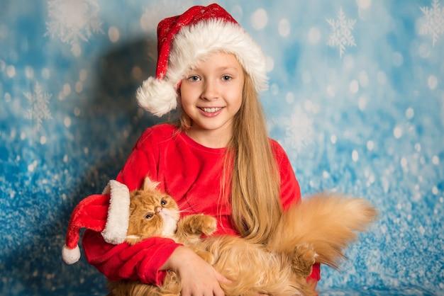 Довольно белокурая девушка с ребенком в красной шляпе санта, держа кошку, изолированную на синем фоне снега. рождественское понятие