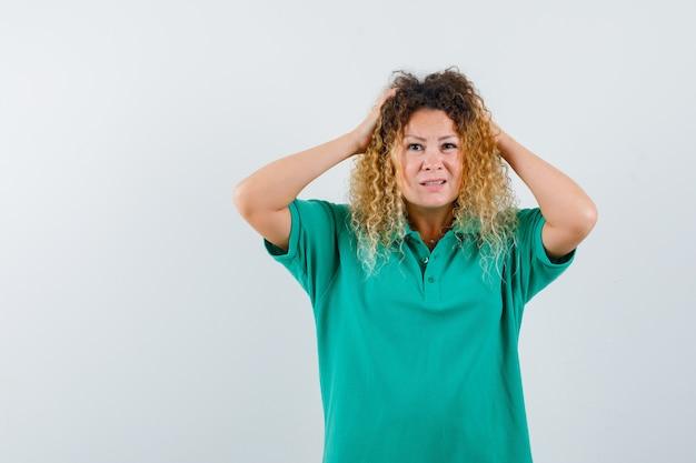 Довольно белокурая дама держит руки на голове в зеленой футболке поло и выглядит беспомощной, вид спереди.