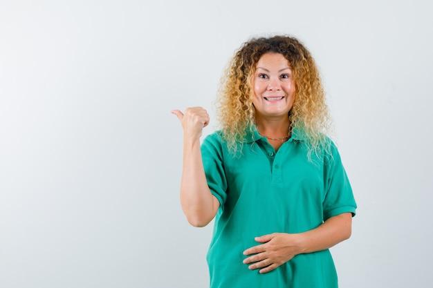 녹색 폴로 티셔츠에 엄지 손가락으로 다시 가리키고 쾌활한 찾고 예쁜 금발 아가씨. 전면보기.