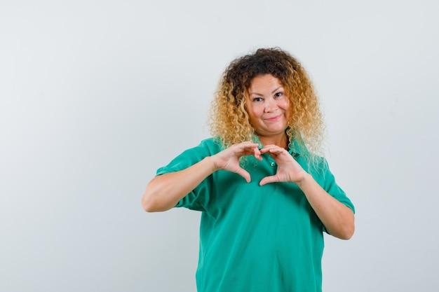 녹색 폴로 티셔츠에 심장 제스처를 표시하고 유쾌한 찾고 꽤 금발 아가씨. 전면보기.