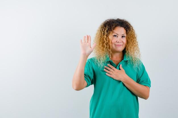 一時停止の標識を示し、緑のポロtシャツで胸に手を保ち、自信を持って見えるかなり金髪の女性。正面図。