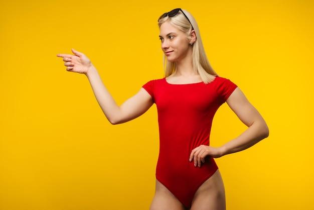 Довольно блондинка спасатель в красном купальнике и солнцезащитных очках указывает пальцем на желтом фоне