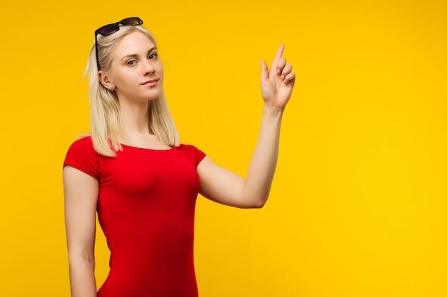 赤い水着とサングラスのかなり金髪のライフガードは黄色の背景に指を指しています