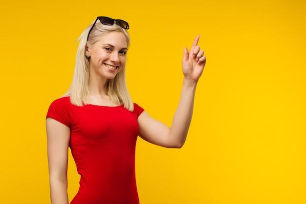 Довольно блондинка спасатель в красном купальнике и солнцезащитных очках указывает пальцем вверх на желтом фоне
