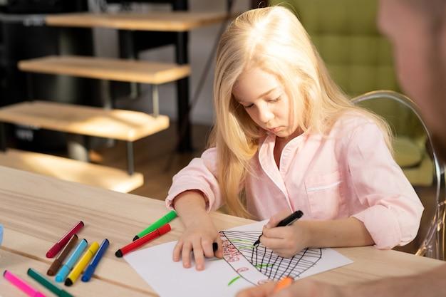 Довольно белокурая маленькая девочка склоняется над деревянным столом, рисуя маркерами на бумаге в домашней обстановке