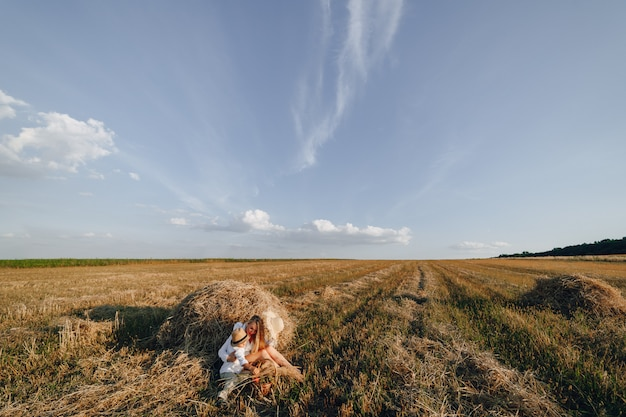 Pretty blond long-haired woman with little blond son at sunset relaxing in the field and savoring fruit from a straw basket. summer, farming, nature and fresh air in the countryside.
