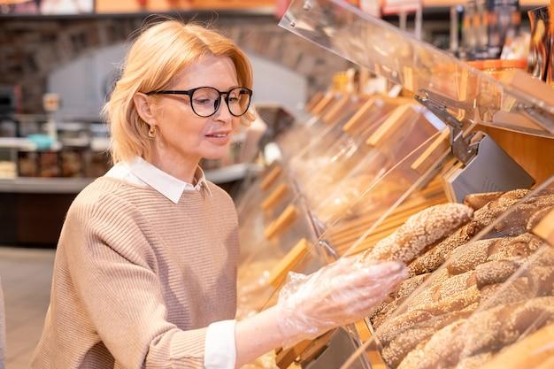 スーパーマーケットで食品を購入しながら、ディスプレイから焼きたてのパンを取るカジュアルウェアと眼鏡のかなり金髪の成熟した女性