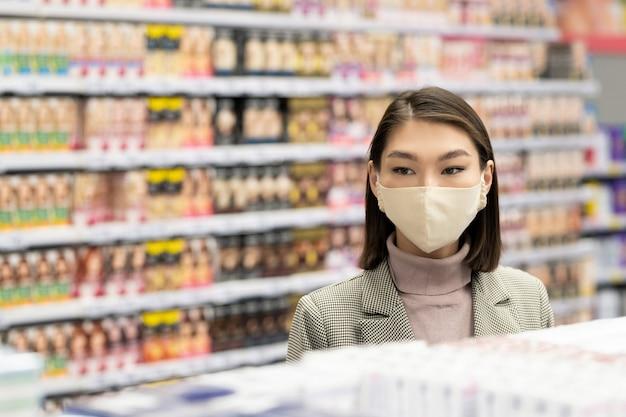 スーパーマーケットで食品を購入しながらディスプレイから焼きたてのパンを取るカジュアルウェアと眼鏡のかなり金髪の成熟した女性
