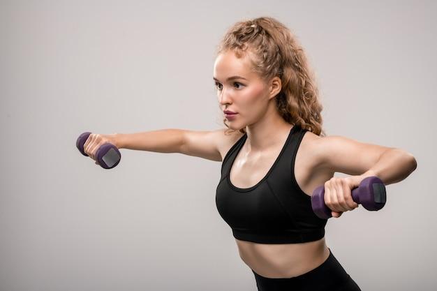 トレーニング中にダンベルで運動しながら灰色の上に立っているアクティブウェアのかなり金髪のスポーツウーマン