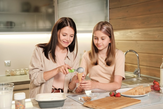 Pretty blond teenage girl standing by kitchen table next to her mother putting tasty homemade icecream into waffle cone over table